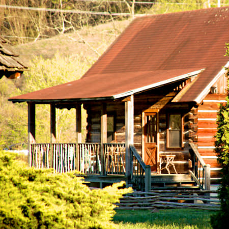 A sunny view of a quaint rustic reddish-brown wood cabin