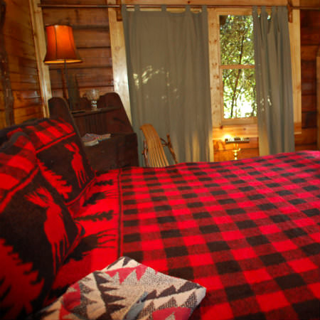 A bright red and black plaid bed lays in the foreground of this rustic guestroom
