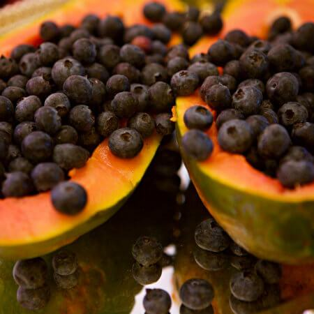 Pink and green papaya halves filled with fresh blueberries