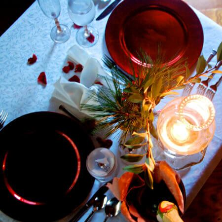 Picture of a table from the top with a candle, wine glasses and plates.