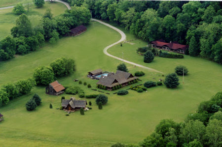 Ariel view of large farm with barn and dirt road and lodge with green trees