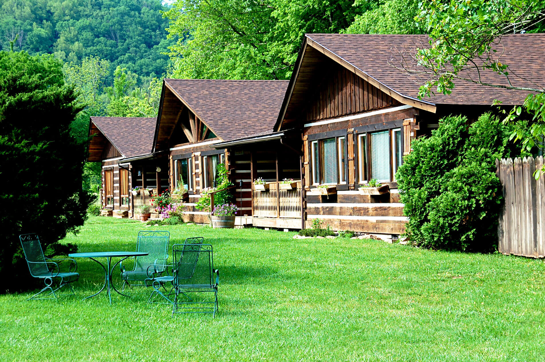 Line of rustic log cabins on green lawn surrounded by big trees