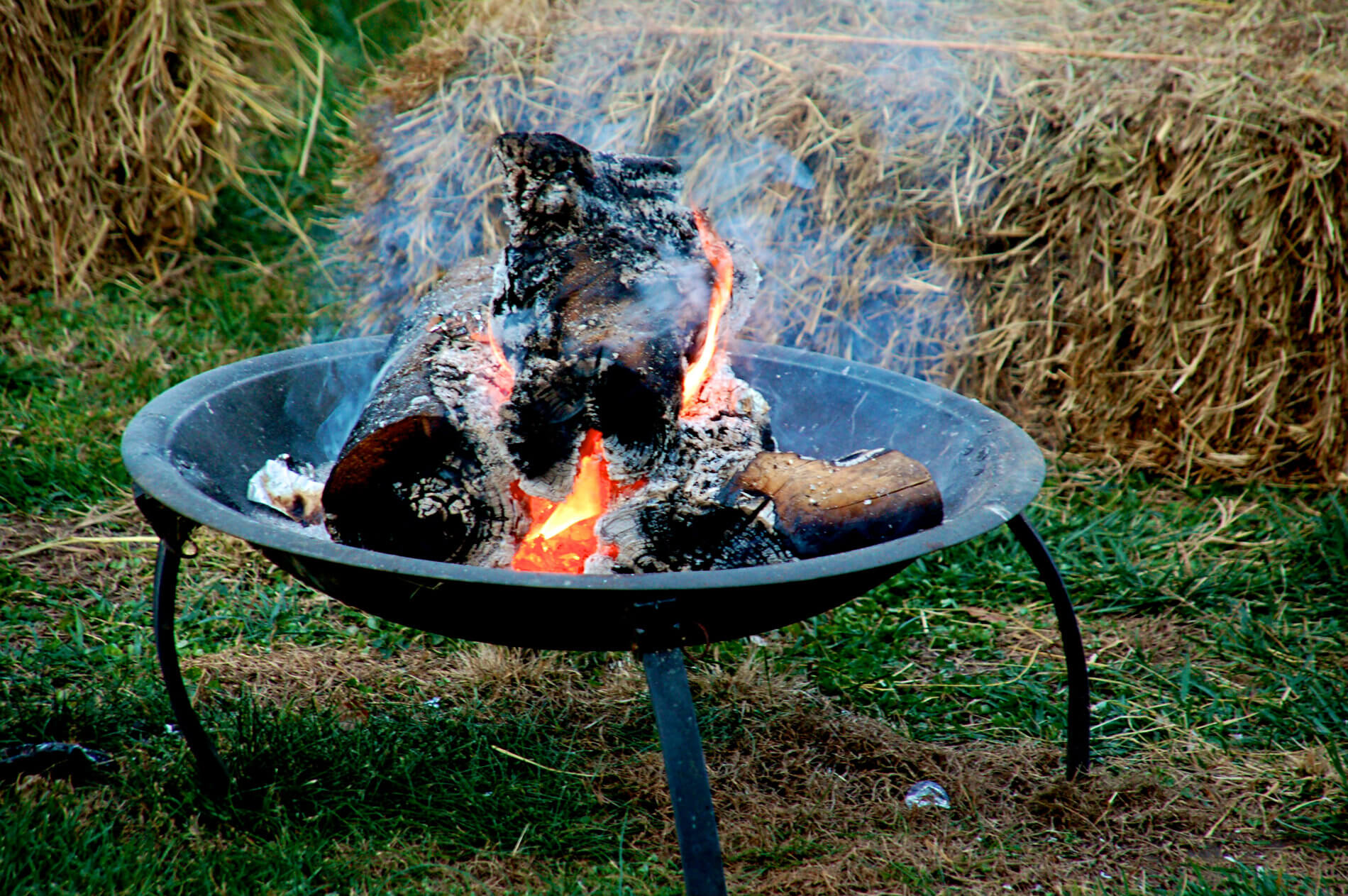 Black iron fire pit with crackling fire in green lawn