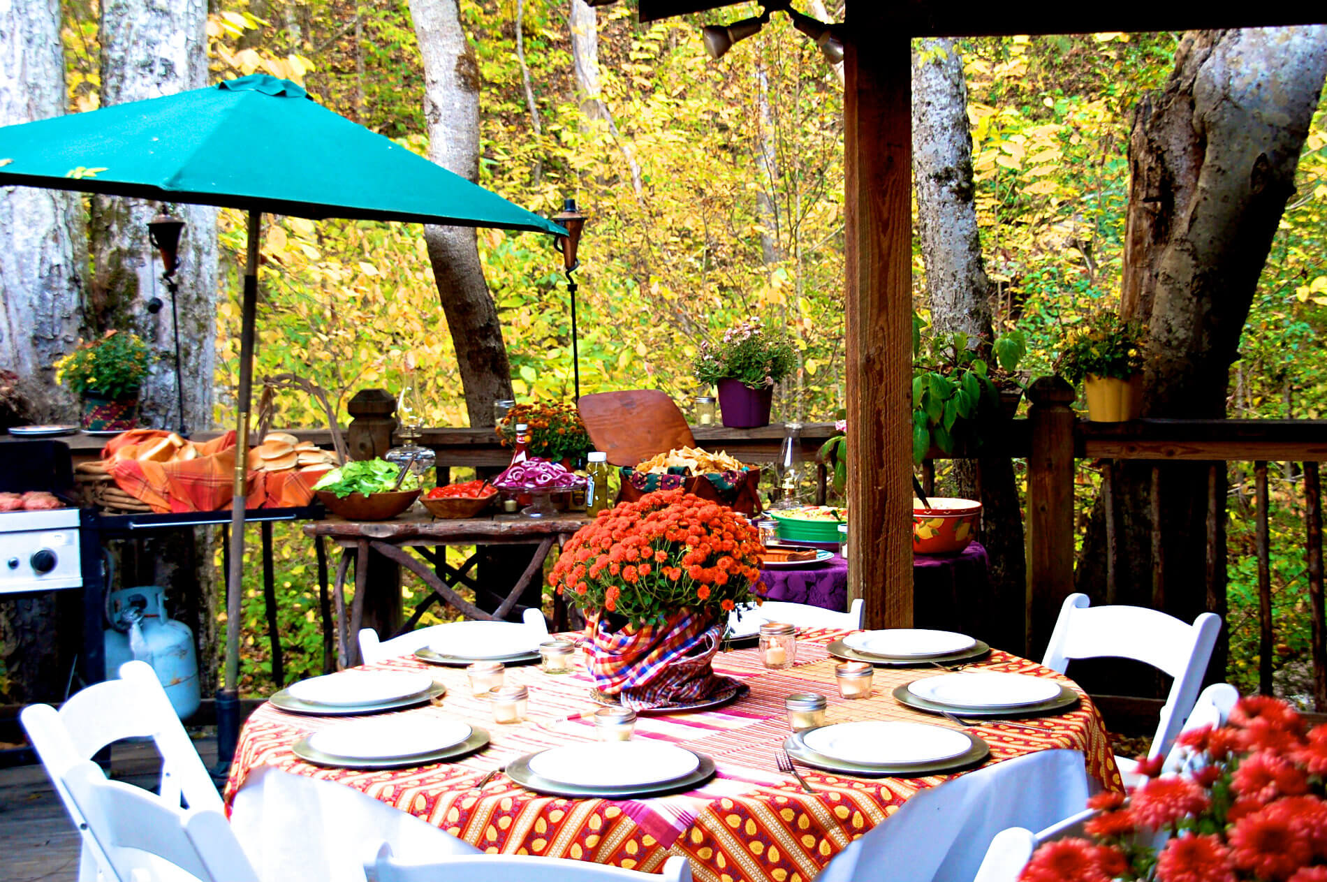 Patio outside next to woods with bright red tablescloths and turquiose umbrellas