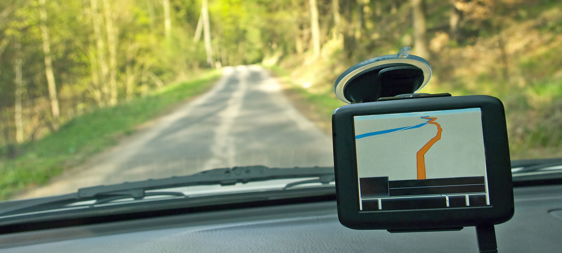 on a windshield a black GPS shows the way through the woods on a windy road