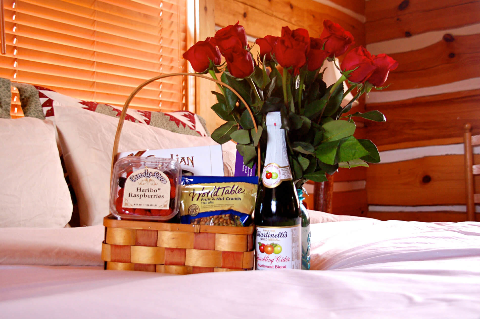 Basket of choclate and other treats with bottle of sparkling cider on a white bedspread with red roses