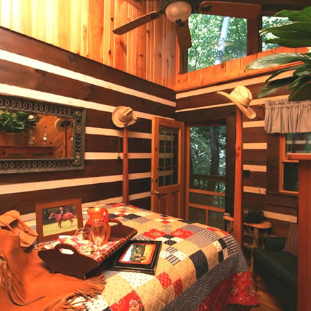 A red, tan and white quilt makes the bed in this cowboy inspired cabin