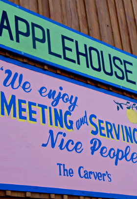 Wooden building with pink, blue and green sign APPLEHOUSE