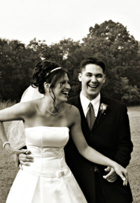 Black and white of bride in strapless gown and groom in black suit laughing