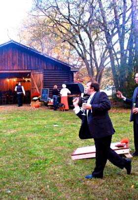 Groomsmen in dark suits playing cornhole outside a barn decorated in fall decor