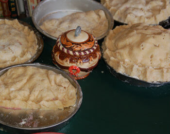 Unbaked double-crust fruit pies on table with small ceramic container