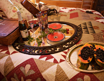 Tray with wine, flowers and wine glasses on patchwork quilt