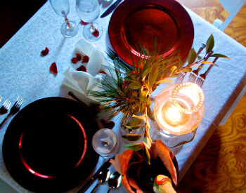 romantic dinner setting with rose petlas, red dishes and oil lamp light light