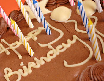 Chocolate cake with candles and HAppy Birthday in yellow frosting