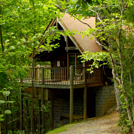 Nestled in the green woods, a two story cabin hides away